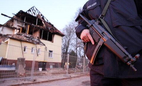 <p> Ein Polizist mit Maschinenpistole steht an der Frühlingsstraße 26 in Zwickau.</p>