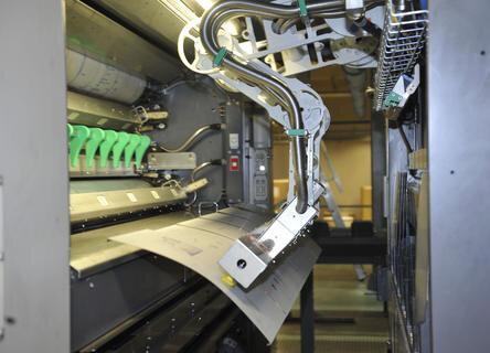 <p> Ein Roboter übernimmt die Plattenwechsel - die innovative Technik spart wertvolle Produktionszeit. Vakuumsaugnäpfe halten die Druckplatten fest.</p>