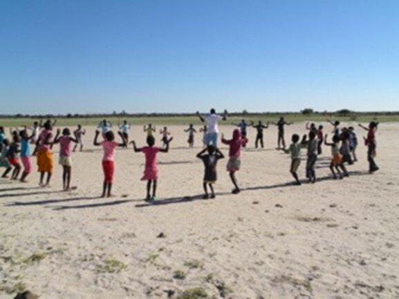 <p> Kinderfest der Mayana Grundschule: Marcus bildet einen großen Kreis mit den Schülern und macht lustige Aufwärmungübungen mit ihnen.</p>