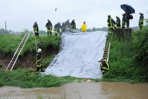 """<p> <span class=""""Text"""">Glauchau/Jerisau: Ein abgerutschter Hochwasserschutzdamm nahe der Kirche (Flutrinne) wird stabilisiert.</span></p>"""