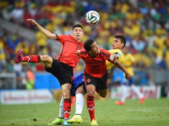 <p> Tänzerisch wenig elegant versuchen der Brasilianer Thiago Silva (r) und die beiden Mexikaner Oribe Peralta (l) und Giovani Dos Santos an den Ball zu kommen. Foto: Georgi Licovski<br /> 17.06.2014 (dpa)</p>
