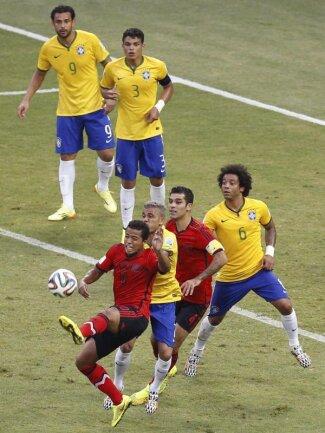 <p> Die Spieler Mexikos und Brasiliens sehen bei einem Freistoß am Sechzehner etwas unglücklich aus. Foto:&nbsp;Chema Moya<br /> 17.06.2014 (dpa)</p>