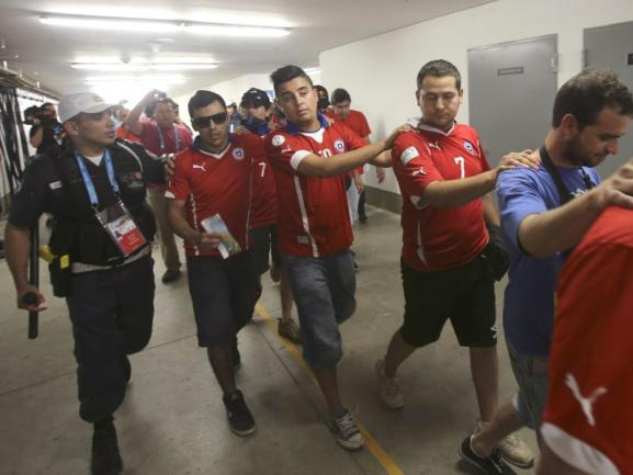 <p> Chilenische Fans hatten vor dem Spiel das Medienzentrum gestürmt. Hier werden sie von den Sicherheitsbeamten abgeführt. Foto: Antonio Lacerda<br /> 18.06.2014 (dpa)</p>