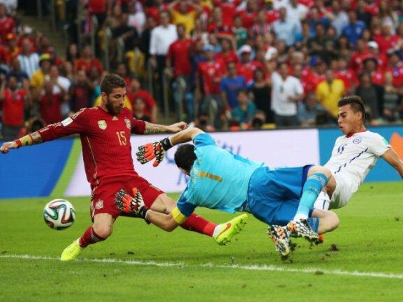 <p> Casillas (M) streckt sich vergeblich und auch Abwehrchef Ramos (l) kommt zu spät: Chiles Angreifer Vargas trifft zum 1:0. Foto: Oliver Weiken<br /> 18.06.2014 (dpa)</p>