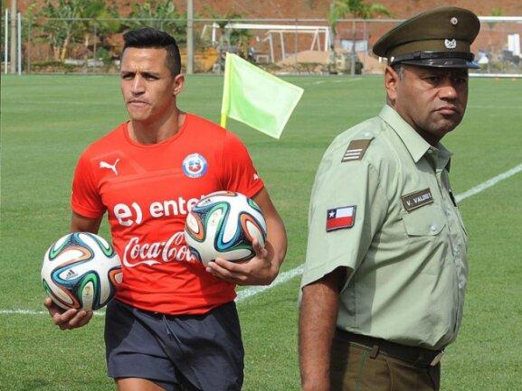 <p> Chiles Alexis Sanchez sichert sich im Rücken der Sicherheitskräfte noch schnell zwei Fußbälle. Foto:&nbsp;Peter Powell<br /> 19.06.2014 (dpa)</p>
