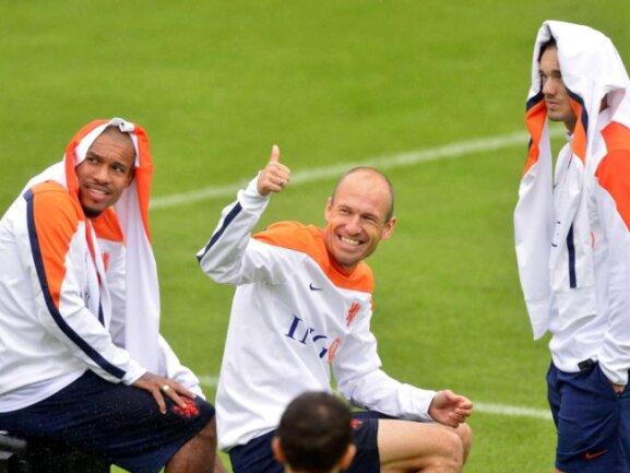 <p> Arjen Robben (M)&nbsp;und seine niederländischen Teamkollegen Nigel de Jong (l) und Wesley Sneijder haben beim Training sichtlich Spaß, auch wenn die Trainingsjacken schon mal als Kopfbedeckungen vor der heißen Sonne Rio de Janeiros herhalten müssen. Foto: Koen van Weel<br /> 19.06.2014 (dpa)</p>