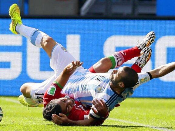 <p> Im Spiel zwischen Argentinien und dem Iran wurde um jeden Zentimeter gekämpft. Auch Irans Reza Ghoochannejhad (u) und Javier Mascherano kamen ins Straucheln. Foto:&nbsp;Dennis Sabangan<br /> 21.06.2014 (dpa)</p>