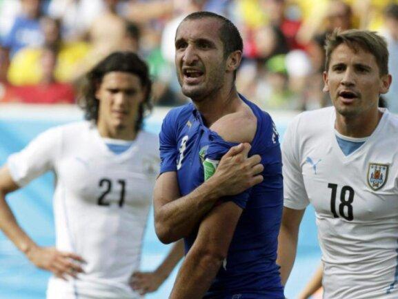 <p> Giorgio Chiellini (M) kann es nicht fassen, Luis Suarez biss dem Italiener in die Schulter. Foto: Emilio Lavandeira Jr<br /> 24.06.2014 (dpa)</p>