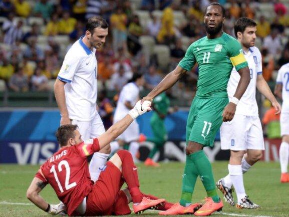 <p> Nach seinem Foul hilft Didier Drogba Griechenlands Torwart Panagiotis Glykos auf die Beine. Foto: Georgi Licovski<br /> 24.06.2014 (dpa)</p>