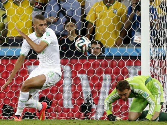 <p> <b>Drin</b><br /> Der Ball ist im Tor, Islam Slimani (l) dreht ab zum Jubeln: Nach einem Fehler von Igor Akinfeew kann Algerien ausgleichen. Foto: Rungroj Yongrit<br /> 26.06.2014 (dpa)</p>