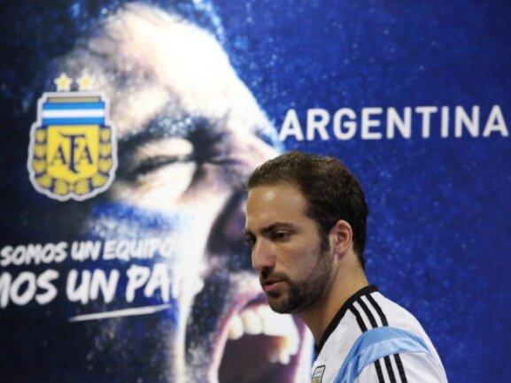<b>Skurril</b><br/>Argentiniens Gonzalo Higuain läuft an einem Werbe-Plakat des eigenen Verbands vorbei, doch es sieht so aus, als beiße Luis Suarez zu. Foto: Jose Coelho<br/>27.06.2014 (dpa)