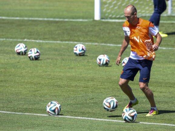 <b>Freie Auswahl</b><br/>Ja, welchen Ball denn nun? Im Training der niederländischen Mannschaft hat Arjen Robben die freie Auswahl, welches Spielgerät er nimmt. Foto: Georgi Licovski<br/>28.06.2014 (dpa)