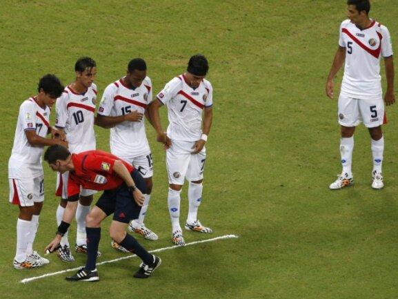 <b>Klare Linienführung</b><br/>Schiedsrichter Benjamin Williams markiert mit dem Farbspray vor Costa Ricas Spielern den Standpunkt der Mauer. Foto: Mast Irham<br/>29.06.2014 (dpa)