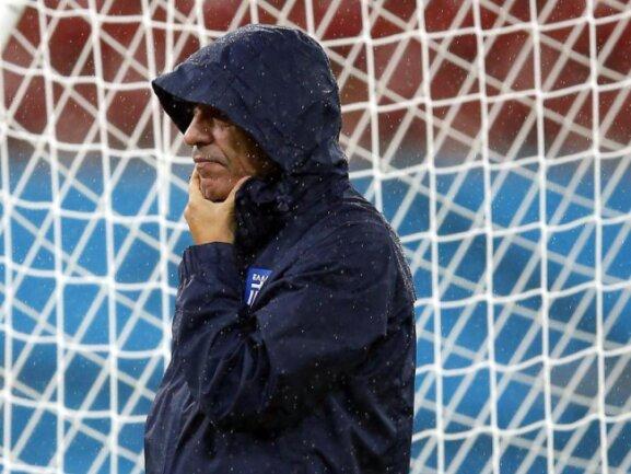 <b>Kapuzenmann</b><br/>Griechenlands Trainer beobachtet bei strömenden Regen das Abschlusstraining seines Teams in der Arena Pernambuco. Foto: Kai Foersterling<br/>29.06.2014 (dpa)