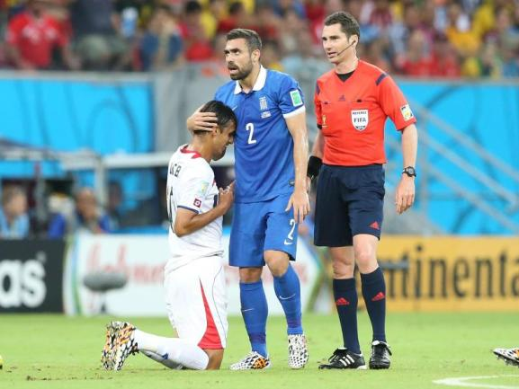 <b>Absolution</b><br/>Nach einem Tackling entschuldigt sich der Grieche Ioannis Maniatis bei Bryan Ruiz von Costa Rica. Foto: Srdjan Suki<br/>29.06.2014 (dpa)