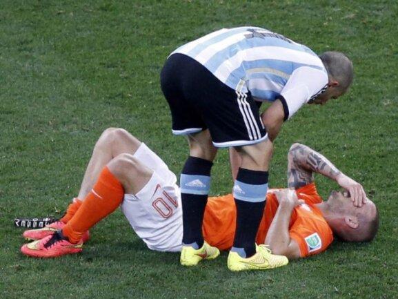 <b>Tut´s weh?</b><br/>Pablo Zabaleta beugt sich zu Wesley Sneijder, der nach einem Tackling am Boden liegt. Foto: Tolga Bozoglu<br/>10.07.2014 (dpa)