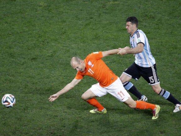 <b>Haltung bewahren</b><br/>Halb zog es ihn, halb sank er hin: Arjen Robben (l) wird vom Argentinier Martin Demichelis am Arm gehalten und verliert dadurch den Ball. Foto:Tolga Bozoglu<br/>10.07.2014 (dpa)