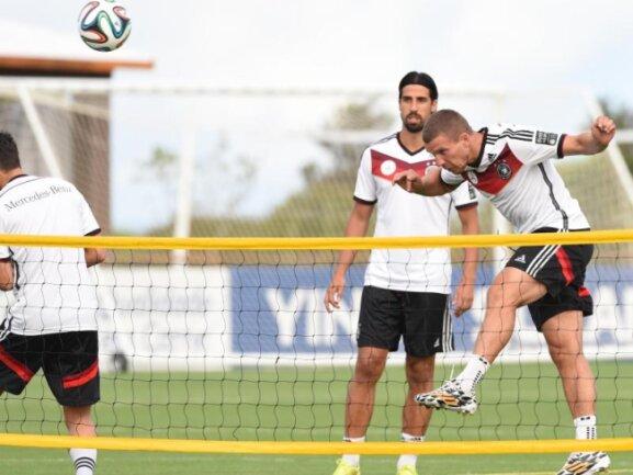 <b>Netzkicker</b><br/>Lukas Podolski (r) spielt den Ball beim Fußballtennis mit dem Kopf über das Netz. Foto: Marcus Brandt<br/>10.07.2014 (dpa)