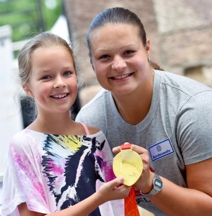 <p> Auch die frischgebackene Weltmeisterin im Kugelstoßen Christina Schwanitz war auf der Sportmeile zu Gast. Charlotte aus Chemnitz durfte die Goldmedaille aus der Nähe betrachten.</p>
