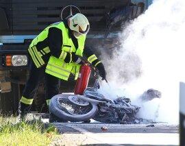 <p> Ein Feuerwehrmann löscht das brennende Motorrad, das vor einem Brummi liegt. Dichte Qualmwolken ziehen über die Straße.</p>