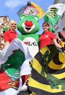 """<p>An der Seite von Maskottchen """"Limbo"""" schwingen Ann-Marie Göbel (l.) und Vanessa Keller von den Schönburger Fahnenschwingern die Fahnen mit dem Wappen der Stadt und dem Wappen des Freistaats.</p>"""
