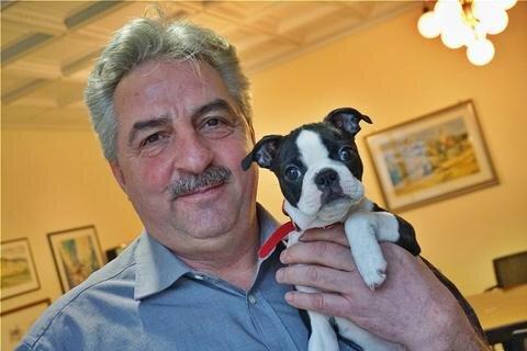 """<p>14. Januar: Oberbürgermeister Manfred Deckert ist auf den Hund gekommen. Sein Dienstzimmer teilt sich Auerbachs Stadtoberhaupt zu Jahresbeginn immer häufiger mit Hundedame Frieda – und nicht nur Besucher finden das niedlich. Das jüngste Familienmitglied darf dem OB aufgrund seines Alters Gesellschaft leisten:<br /> """"Frieda ist so jung, dass man sie noch nicht längere Zeit alleine zu Hause lassen kann."""" Inzwischen ist die Bostonterrier-Hündin kräftig gewachsen – und das Körbchen unterm OB-Schreibtisch meistens leer.</p>"""