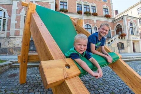 """<p>25. Juli: Der vierjährige Henry und sein zehnjähriger Bruder Eric Zielinski (v. l.) aus Stollberg freuen sich über den neuen und sauberen Liegestuhl in der Größe XXL, der nun seinen dreckigen, bemalten Vorgänger vor dem Rathaus in Stollberg abgelöst hat. Die beiden klettern fast täglich auf den Stuhl, wenn sie mit den Eltern daran vorbeikommen. """"Der alte Stuhl hat wirklich ausgedient, also haben wir einen neuen hergestellt"""", sagt Marcus Schmidt, der Chef der Dienstleistungsgesellschaft Stollberg. Kosten für die Neuanschaffung betragen laut Schmidt etwa 1500 Euro. Der etwa sechs Jahre alte Vorgänger-Stuhl sei wegen der glücklicherweise häufigen Benutzung schon schlimm verschlissen, wacklig und das Holz teilweise vom Schwamm befallen gewesen. """"Der neue soll nun länger halten"""", hofft Schmidt. Dafür habe man extra Lärchenholz benutzt, dieses wiederum mit Dünnschichtlasur behandelt.</p>"""