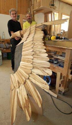 """<p>15. September: Einen Adler aus hauchdünnen Schindeln von Zebranoholz fertigt Holzgestalter Andreas Schmidt, der im Team der Firma Massivholz-Design in Langenberg arbeitet. """"Dieser Adler ist ein Auftragswerk für einen Kunden aus der Region"""", erläutert Firmeninhaber Mario Günther. Nach zahlreichen Skizzen und Zeichnungen wurde zunächst ein Grundkörper aus Fichtenholz gefertigt, der die 3.80 Meter Flügelspannweite des hölzernen Seglers stützt.</p>"""