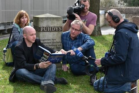 """<p>5. April: Anfang des Jahres gaben die Puhdys ihr letztes Konzert in Berlin. Doch mit Freiberg wird die Kult-Rock-Band ewig verbunden sein. Das beschreibt Buchautor Thomas Reibetanz (2. v. l.) in seinem Buch """"Auf Lebenszeit"""". Ein Team des MDR machte den Autor und Volker Doberstein<br /> (3. von links), einen Puhdys-Fan der ersten Stunde, zum Mittelpunkt eines Beitrags. Gedreht wurde am Gedenkstein unter der Puhdys-Eiche am Konzerthaus """"Tivoli"""".</p>"""