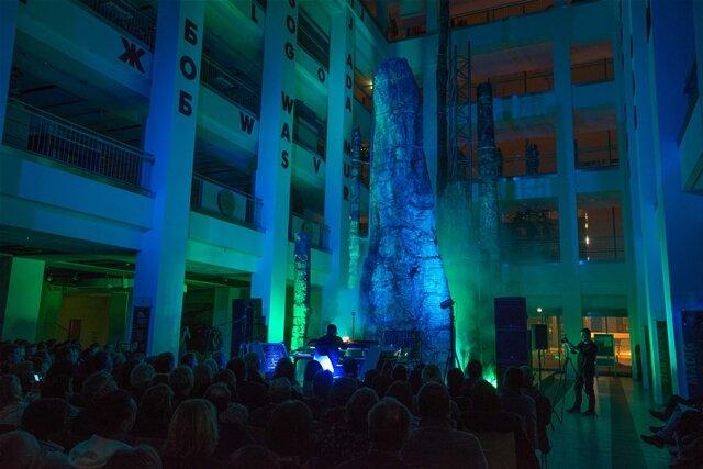 <p>Am Abend wallte schließlich farbiger Trockeneisnebel, Nebelwände stiegen zwischen den Stämmen im 25 Meter hohen Lichthof des Kulturkaufhauses auf, Laserblitze zuckten und die Stämme glühten rot auf.</p>