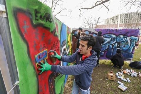 <p>Ali Reza Hosseiniaus aus Afghanistan besprüht diese Leinwand im Stadthallenpark.</p>