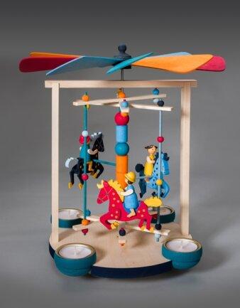 """<p><strong>Karussellpyramide, Einreicher: Graupner Holzminiaturen, Crottendorf, 30 cm hoch</strong><br /> &nbsp;</p>  <p>""""Die Karussellpyramide stellt eine Verbindung von traditionellem erzgebirgischen Spielzeugkarussell und<br /> der klassischen Kerzenpyramide dar.""""</p>  <p>Katrin Baumann<br /> Gestalterin</p>"""