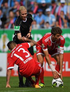 <p>Schiedsrichterin Bibiana Steinhaus hilft neben Thomas Müller (r) Bayerns Rafinha auf die Beine.</p>