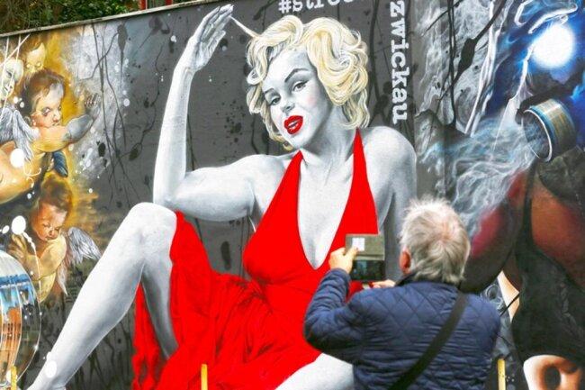 <p>Auch Marilyn Monroe lächelt lasziv im roten Kleid von der Wand.</p>