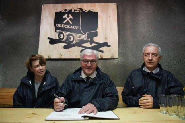 <p>Bundespräsident Frank-Walter Steinmeier (mittig) trägt sichbei seinem Besuch in der Grube Niederschlag neben seiner Frau Elke Büdenbender und Sachsens Ministerpräsident Stanislaw Tillich (CDU) in ein Buch ein.</p>