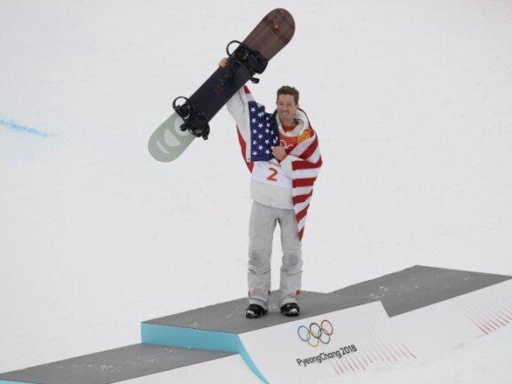 <b>Stars and Stripes</b><br/>In die USA-Flagge eingehüllt jubelt Snowboard-Superstar Shaun White über sein Gold in der Halfpipe. Foto: Kin Cheung<br/>14.02.2018 (dpa)