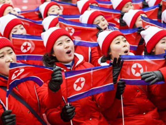 <b>Synchron</b><br/>Cheerleader aus Nordkorea schwenken ihre Fahnen auf der Tribüne des Yongpyong Alpin-Zentrums. Foto: Jean-Christophe Bott/KEYSTONE<br/>14.02.2018 (dpa)
