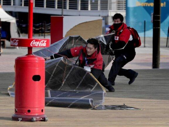 <b>Anschnallen, bitte</b><br/>Verkäufer kämpfen gegen den starken Wind im Olympia-Park und versuchen ihren Stand zu sichern. Wegen starker Winde wurden mehrere Wettkämpfe abgesagt. Foto: Julie Jacobson<br/>14.02.2018 (dpa)