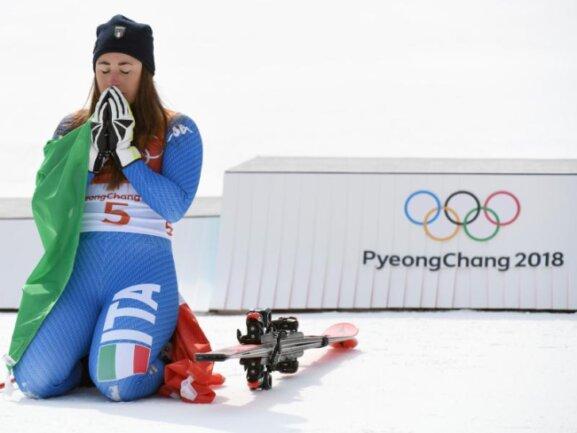 <b>Moment</b><br/>Auf dem Schnee knieend genießt Abfahrtssiegerin Sofia Goggia aus Italien bei der Siegerehrung ihren Erfolg. Foto:Tobias Hase<br/>21.02.2018 (dpa)