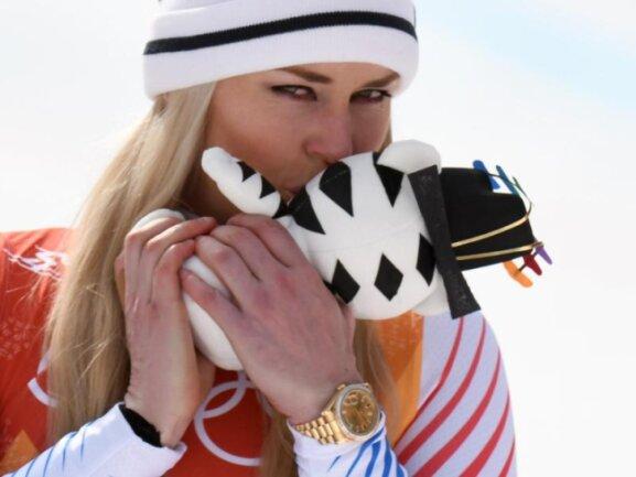 <b>Abgeknutscht</b><br/>Lindsey Vonn freut sich über Bronze in der Abfahrt und küsst das Maskottchen bei der Siegerehrung. Foto: Tobias Hase<br/>21.02.2018 (dpa)