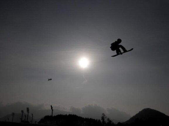 <b>In luftiger Höhe</b><br/>Der Mond steht am Himmel während Goldmedaillengewinner Sebastien Toutant aus Kanada beim Training für den Big Air Snowboard Wettbewerb springt. Foto: Matthias Schrader/AP<br/>24.02.2018 (dpa)