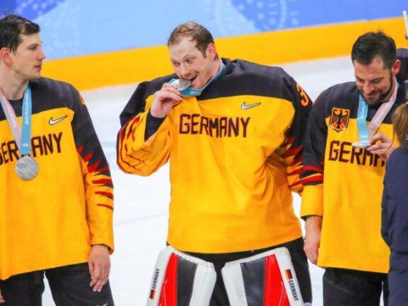 <b>Bissfest</b><br/>Deutschlands Eishockey-Torwart Danny aus den Birken (M.) spürt den Geschmack der olympischen Silbermedaille. Foto: Michael Kappeler<br/>25.02.2018 (dpa)
