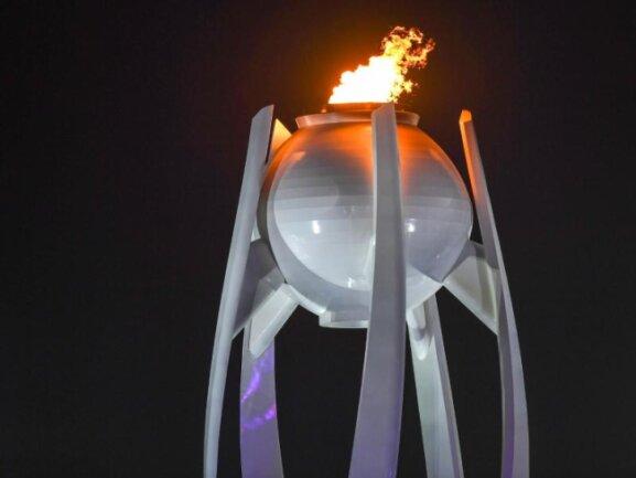 <b>Bald erloschen</b><br/>Das Olympische Feuer brennt (noch) während der Schlussfeier über dem Olympiastadion in Pyeongchang. Foto: Hendrik Schmidt<br/>25.02.2018 (dpa)