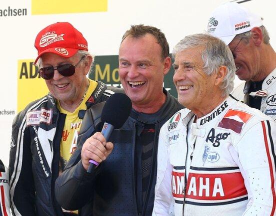 <p>90 Jahre Sachsenring 2017: Star des Wochenendes außer Zweifel der 15-fache Weltmeister Giacomo Agostini aus Bergamo/Italien (rechts), hier mit Ralf Waldmann am Mikrofon und Phil Read 8-facher Weltmeister bei der Verabschiedung von den Fans.&nbsp;</p>