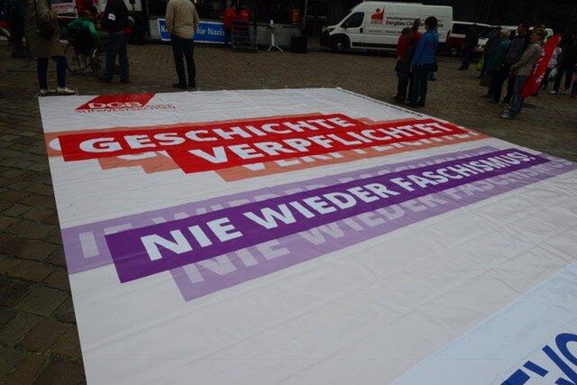 """<p>In der Mitte des Marktplatzes liegt ein Großplakat der DGB-Gewerkschaften: """"Geschichte verpflichtet. Nie wieder Faschismus."""". Die DGB-Ordner tragen """"Refugees welcome""""-Westen.</p>"""