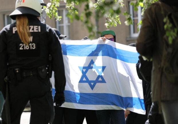 <p>Teilnehmer einer der Demonstration gegen Rechts halten eine Flagge Israels hoch.</p>