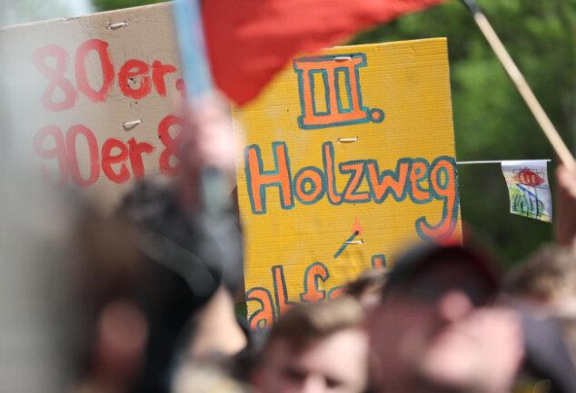 """<p>Teilnehmer einer Gegendemonstration protestieren und halten ein Schild mit der Aufschrift """" III. Holzweg"""".</p>"""