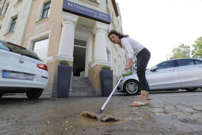 <p>Silke Bethmann kehrt Wasser und Schlamm vor ihrem Laden auf dem Kaßberg weg.</p>