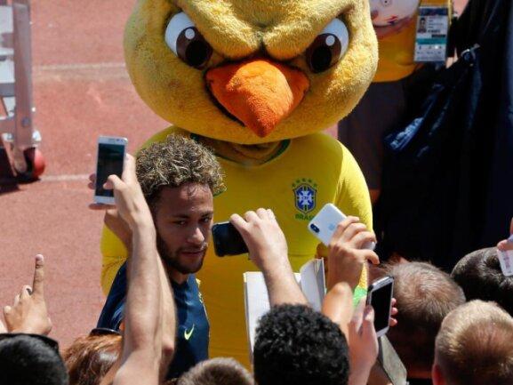 <p><b>«Wingman»</b><br /> «Flügelmann» Canarinho, das Maskokttchen der brasilianischen Nationalmannschaft, ein etwas böse blickender Kanarienvogel, wacht über Fußball-Superstar Neymar, der beim Trainingsgeländer von Fans belagert wird. Foto:Andre Penner<br /> 14.06.2018 (dpa)</p>
