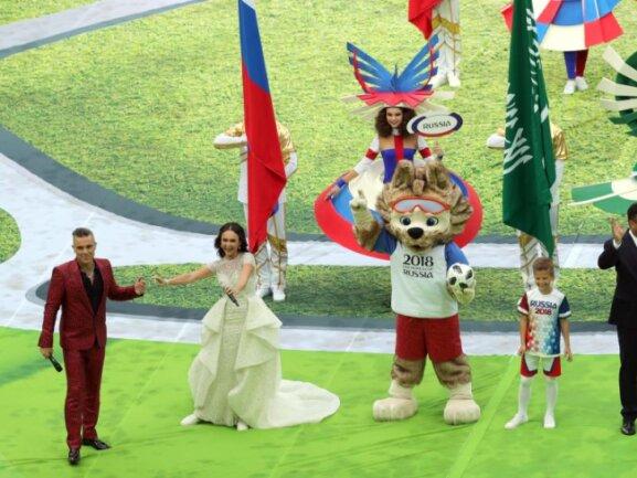 <p><b>Drei Weltstars und ein Wolf</b><br /> Popstar Robbie Williams, die russische Opernsängerin Aida Garifullina, WM-Maskottchen «Sabiwaka» und der frühere brasilianische Fußball-Star Ronaldo bei der Eröffnungsfeier der Fußball-WM im Moskauer Luschnikistadion. Foto: Christian Charisius<br /> 14.06.2018 (dpa)</p>